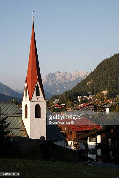 Church tower of St. Oswald church with town of Seefeld in background.