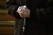 A churchgoer holds a cross and rosary beads as the head of the Catholic Church in Ireland Cardinal Sean Brady speaks in SaintPatricks Cathedral on...