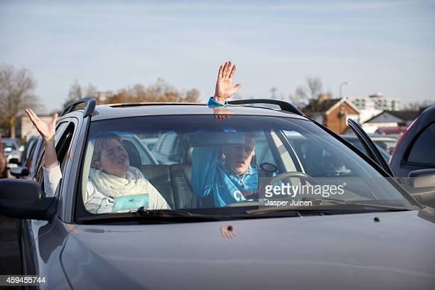 Churchgoers raise their hands while singing inside their car during a drivein church service of the Evangelical church Mosaic 0318 on November 23...