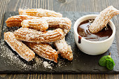 Churros with hot chocolate and powdered sugar.