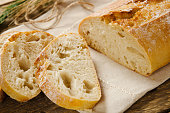 Ciabatta bread. Slices of ciabatta on a wooden table on linen cloth. Rustic, rustic style. Top view, background