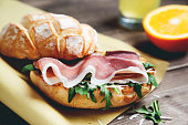 ciabatta bread prosciutto parmesan and arugula in paper with orange  juice on background top view