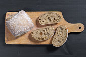 Loaf of ciabatta bread and slices on cutting board on black wooden background, top view