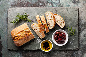 Fresh ciabatta with olive oil and olives on stone slate background