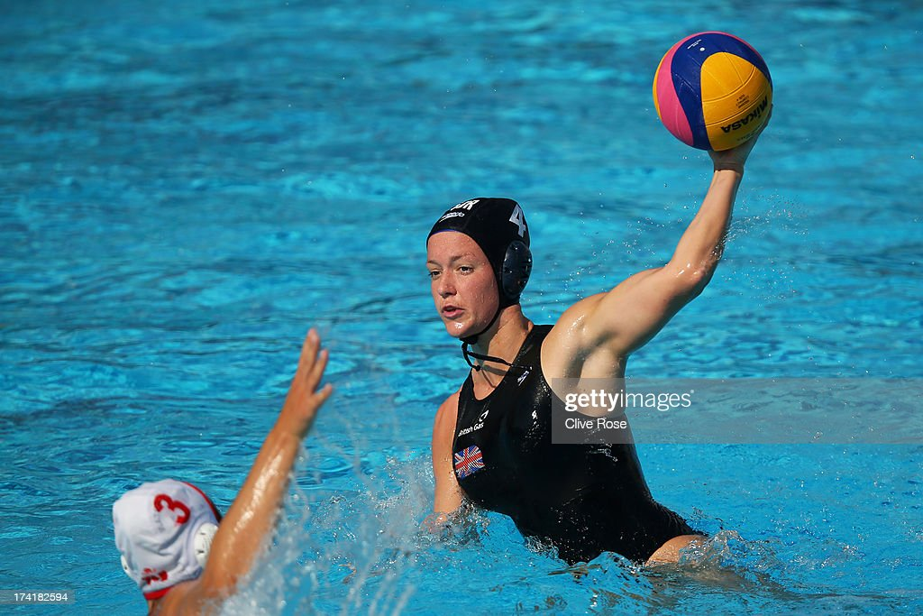 Ciara Gibson-Byrne of Great Britain looks to pass a ball under pressure from Katrina Monton of Canada in the Women's Water Polo first preliminary round match between Canada and Great Britain during Day Two of the 15th FINA World Championships at Piscines Bernat Picornell on July 21, 2013 in Barcelona, Spain.