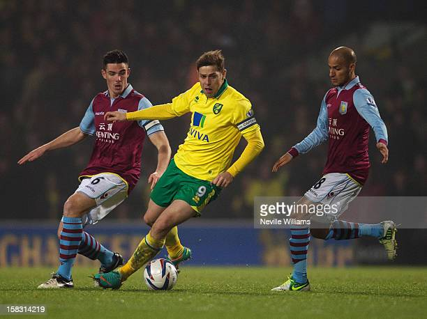 Ciaran Clark and team mate Karim El Ahmadi of Aston Villa challenge Grant Holt of Norwich City during the Capital One Cup Quarter Final match between...