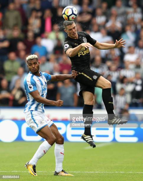 Ciaran Clark of Newcastle United outjumps Steve Mounie during the Premier League match between Huddersfield Town and Newcastle United at John Smith's...