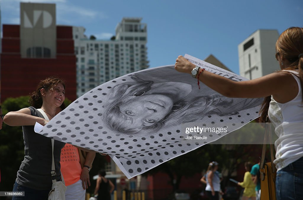 Cicilia Chaar (L) and Karla de Anda hold a photograph as they participate in the 'Inside Out 11M' project on August 31, 2013 in Miami, Florida. The public art project puts a face on immigration reform by creating a massive mosaic of portraits taken on site, printed immediately and pasted on the Freedom Tower at Miami-Dade College.