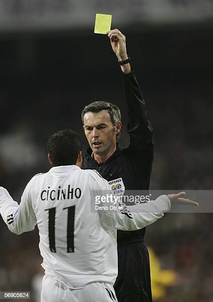 Cicinho of Real Madrid gets a yellow card from referee Stefano Farina during a UEFA Champions League match between Real Madrid and Arsenal at the...