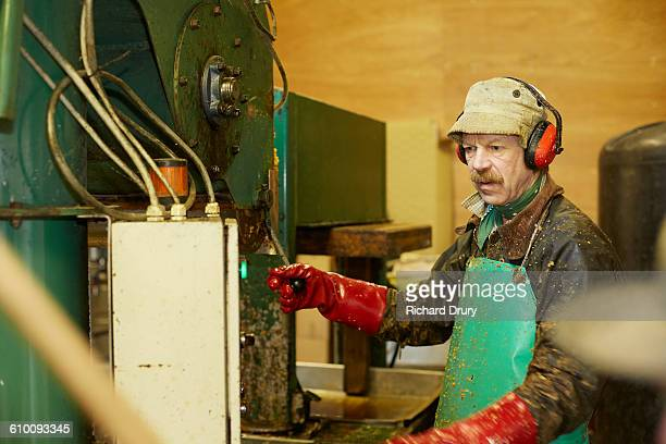 Cider maker operating apple pressing machine