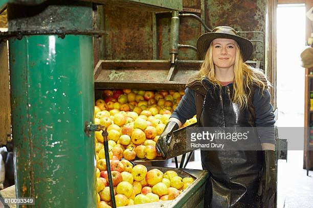 Cider maker standing by apple pressing machine