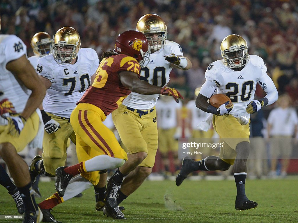 Cierre Wood #20 of the Notre Dame Fighting Irish carries the ball as he gets a block from Tyler Eifert #80 on Josh Shaw #26 of the USC Trojans during a 22-13 Notre Dame win at Los Angeles Memorial Coliseum on November 24, 2012 in Los Angeles, California.