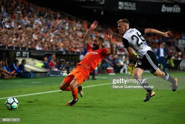 Cifuentes of Malaga is tackled by Antonio Latorre Lato of Valencia during the La Liga match between Valencia and Malaga at Estadio Mestalla on...