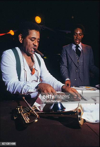 A cigar in his mouth American Jazz musician Dizzy Gillespie cuts a piece of cake during a party for his 60th birthday at the Jazz Showcase Chicago...