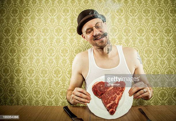 Cigar Puffing Man Displaying Heart Shaped Steak on White Plate