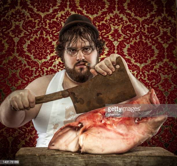 Cigar Smoking Butcher Holding Cleaver Against a Boars Head