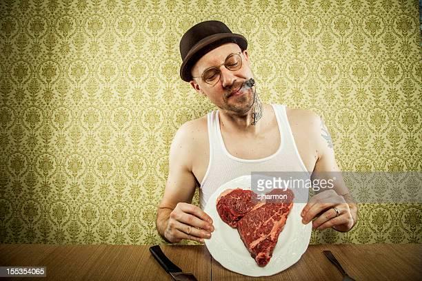 Zigarre rauchen Mann hält einen herzförmigen Steak