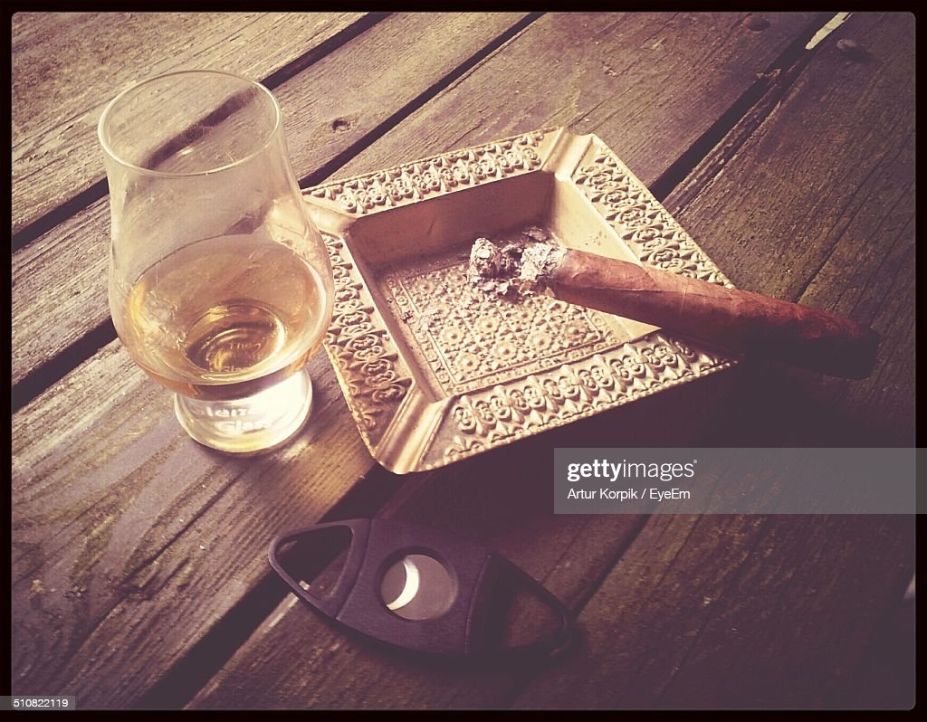 Cigar with cutter and glass of alcohol on table