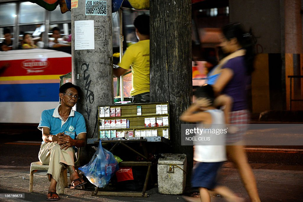 Cigaratte vendor Alex Santiago waits for customers on a street in Manila on November 21, 2012. The Philippines has moved closer to raising tobacco and alcohol taxes, the government said on November 21 after the Senate passed a bill aimed at weaning millions of smokers off the habit.