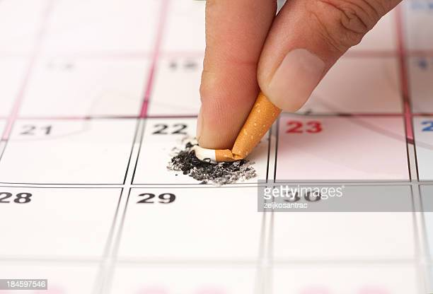 Cigarette being stubbed out on a calendar date