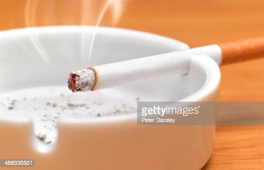 Cigarette in ash tray : Stock Photo
