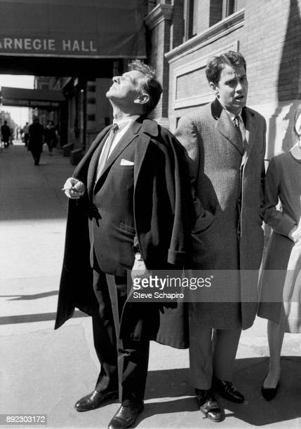 A cigarette in his band American composer musician and conductor Leonard Bernstein stands on the sidewalk outside Carnegie Hall and looks up eyes...
