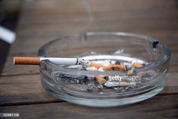 A cigarette lies in an ashtray in Essen western Germany on July 6 2010 Buoyed by a referendum victory for a total ban on smoking in public places in...