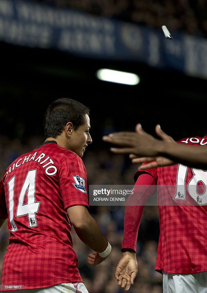 """A cigarette lighter (top right) flies past Manchester United's Mexican player Javier Hernandez (L) after he scores their third goal during the English Premier League football match between Chelsea and Manchester United at Stamford Bridge in London, on October 28, 2012. Manchester United won the game 3-2. USE. No use with unauthorized audio, video, data, fixture lists, club/league logos or """"live"""" services. Online in-match use limited to 45 images, no video emulation. No use in betting, games or single club/league/player publications."""