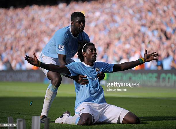 A cigarette lighter is thrown onto the pitch as Emmanuel Adebayor of Manchester City celebrates with teammate Kolo Toure in front of the Arsenal fans...