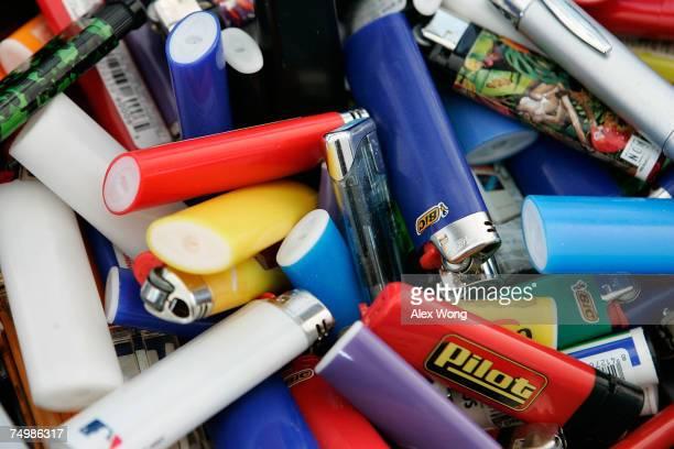 Cigarette lighters that were confiscated by luggage screeners in the morning hours sit in a pile at Dulles International Airport July 2 2007 in...
