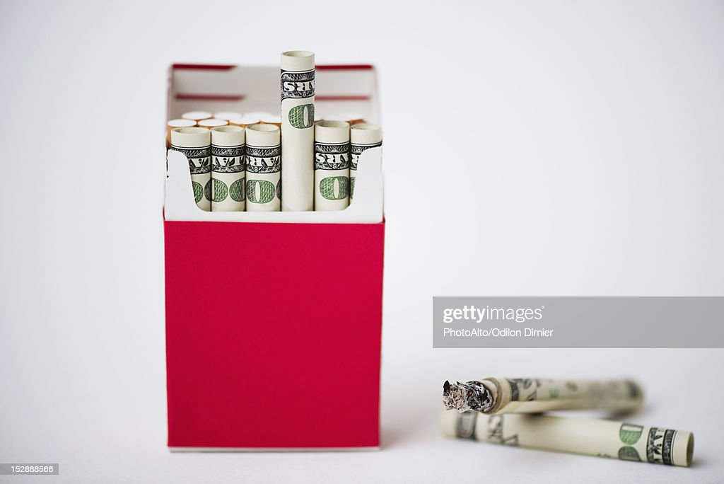 Cigarette pack containing rolled dollars : Stock Photo