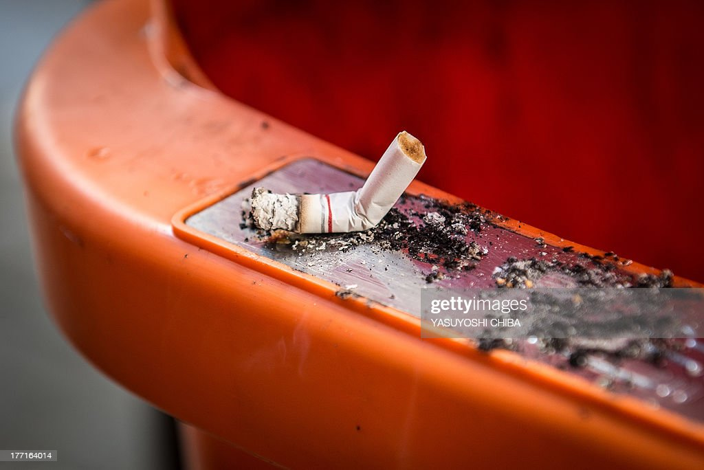 A cigarette stub put out on the ad hoc metal edge of a dustbin in downtown Rio de Janeiro, Brazil on August 21, 2013. The new municipal regulation 'LIXO ZERO' (Zero trash), imposes fines from 157 to 3000 reais (about 65 to 1250 USD) to the offenders. AFP PHOTO / YASUYOSHI CHIBA