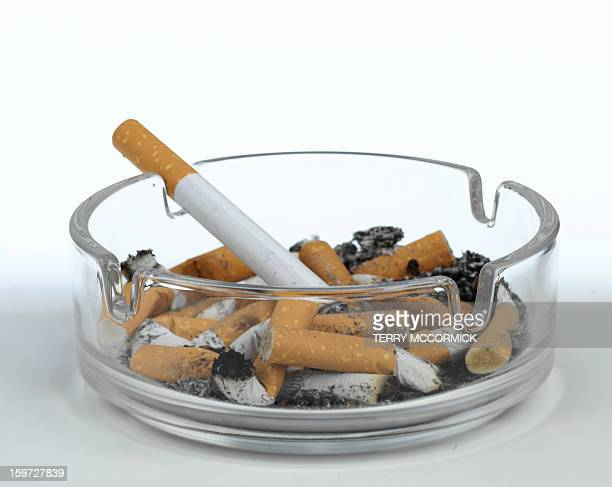Cigarettes and butts in glass ashtray