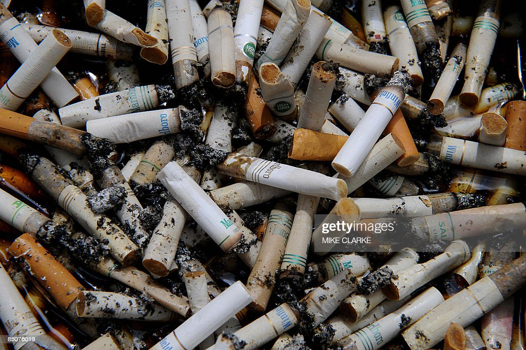 Cigarettes butts in an ashtray at a smoking zone in Hong Kong on February 25, 2009. The territory's economy will shrink by between 2.0 and 3.0 per cent according to Financial Secretary John Tsang in his annual budget speech as Hong Kong slips further into recession. Taxes were raised on cigarettes by 50 per cent. AFP PHOTO/MIKE CLARKE