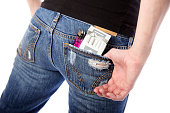 A close-up of a woman's jeans with cigarettes and a lighter in her back pocket.