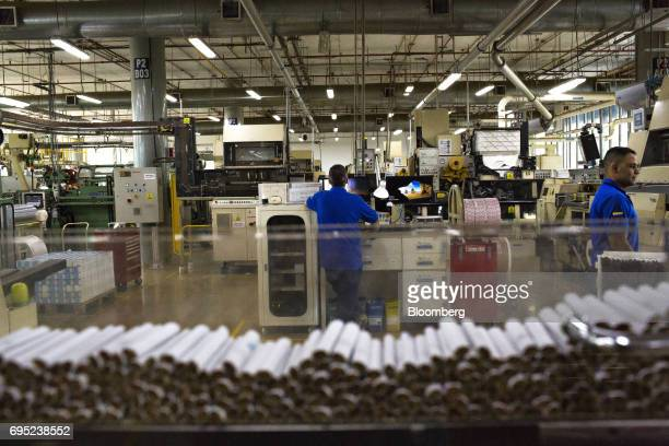Cigarettes moves along a machine during the assembly process at the Philip Morris International Coltabaco SAS production facility in Medellin...