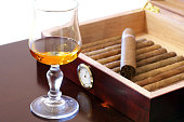 Fine Cuban cigars and glass of rum on wooden table