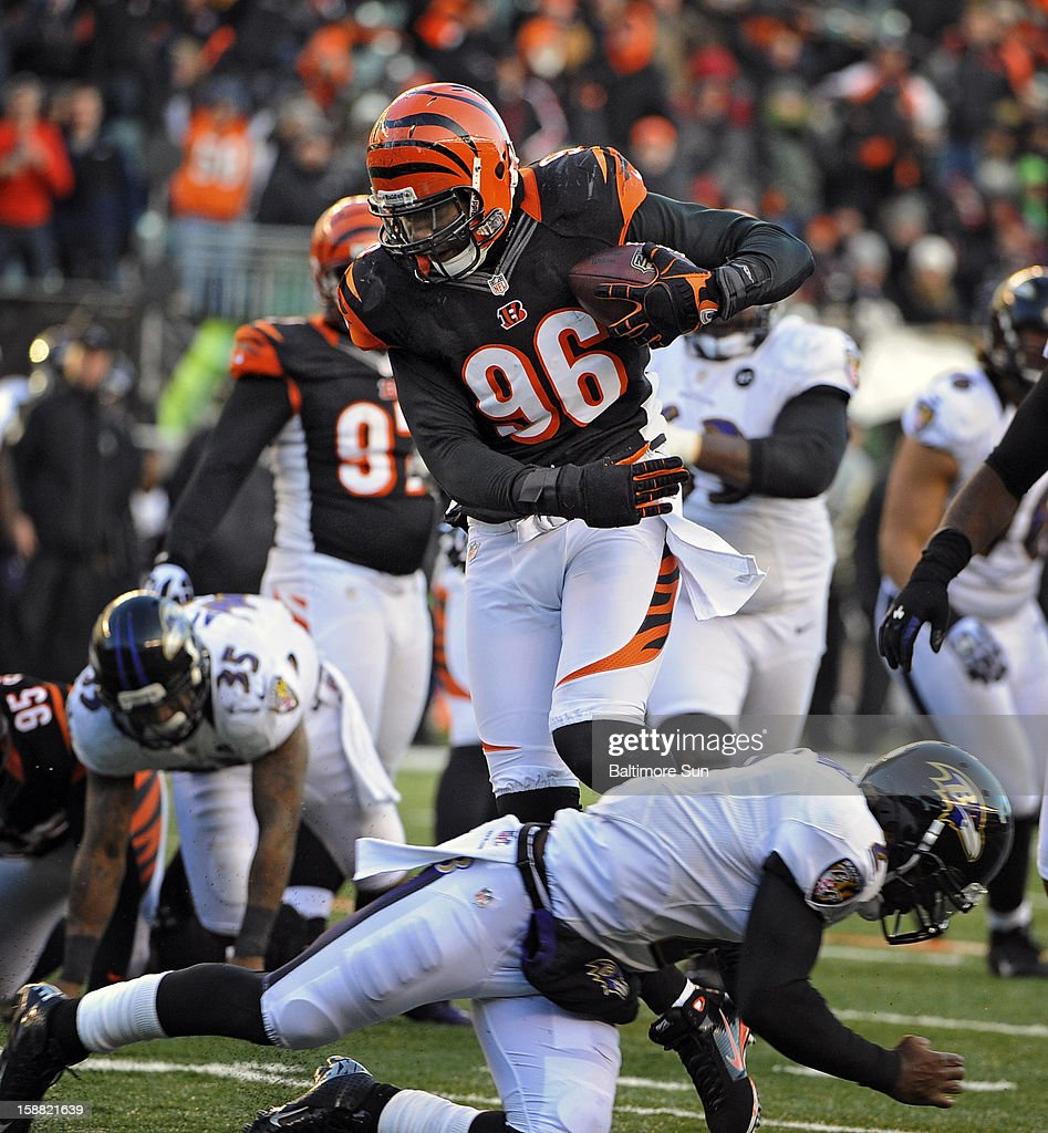 Cincinnati Bengals' Carlos Dunlap (96) runs for a touchdown on an interception as he avoids Baltimore Ravens quarterback Tyrod Taylor, bottom, in the fourth quarter at Paul Brown Stadium on Sunday, December 30, 2012, in Cleveland, Ohio. The Cincinnati Bengals defeated the Baltimore Ravens, 23-17.