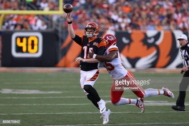 Cincinnati Bengals quarterback Andy Dalton throws a pass while Kansas City Chiefs outside linebacker Dee Ford makes a tackle during the preseason...