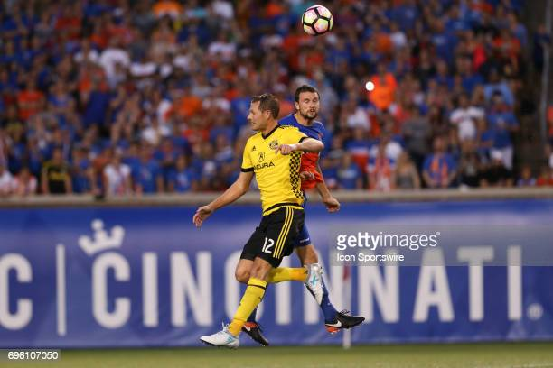 Cincinnati defender Austin Berry headers a ball with Columbus Crew SC forward Adam Jahn defending during the match between the Columbus Crew SC and...