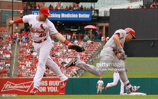 Cincinnati Reds' Adam Duvall right reaches first base past the tag attempt by St Louis Cardinals first baseman Luke Voit in the second inning during...