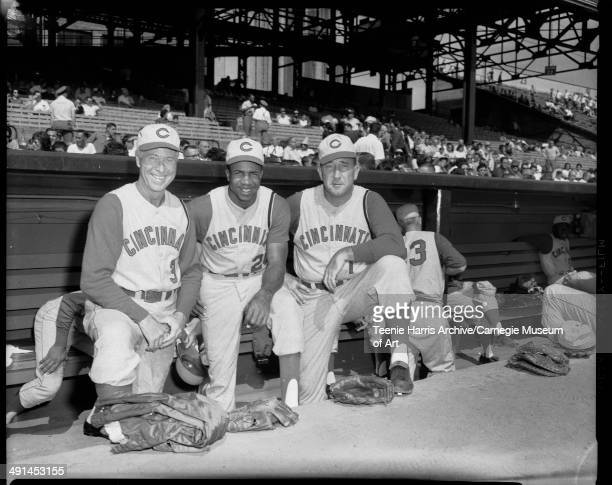 Cincinnati Reds baseball team members from left pitching coach Jim Turner Frank Robinson and manager Fred Hutchinson standing in dugout at Forbes...