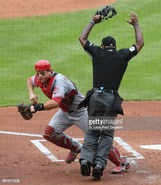 Cincinnati Reds catcher Devin Mesoraco tries to get around home plate umpire Alan Porter as he chases after a passed ball on a walk to St Louis...