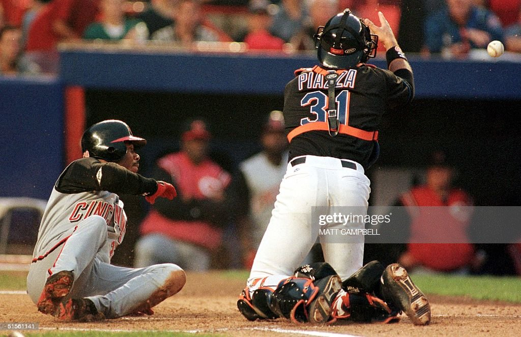 Cincinnati Reds center fielder Ken Griffey Jr. (L) rolls past New York Mets catcher Mike Piazza to score a run as Piazza can't hold the ball in the top of the first inning 31 July, 2000 at Shea Stadium in Flushing, NY. Griffey scored on a double by Reds right fielder Dante Bichette. AFP PHOTO/Matt CAMPBELL