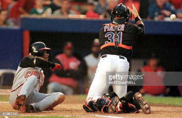 Cincinnati Reds center fielder Ken Griffey Jr rolls past New York Mets catcher Mike Piazza to score a run as Piazza can't hold the ball in the top of...