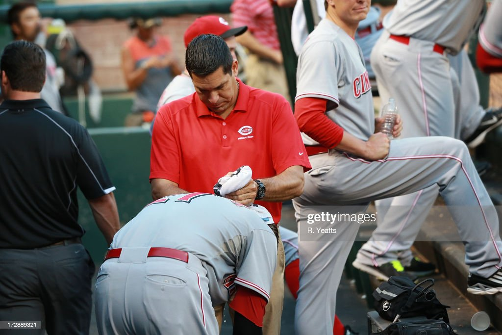 Cincinnati Reds medical staff apply cold towels to the head of Todd Frazier #21 of the Cincinnati Reds to combat the heat between innings of the interleague game against the Texas Rangers at Rangers Ballpark in Arlington on June 28, 2013 in Arlington, Texas.
