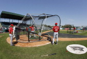 Cincinnati Reds players take batting practice prior to Sunday's game against the Pittsburgh Pirates at McKechnie Field in Bradenton Florida on March...
