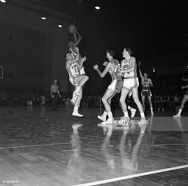 Cincinnati's Big 'O' Oscar Robertson makes a bank shot for a sinker worth two off the side and shoulder of Hawk's Al Ferrari As Robertson went up...