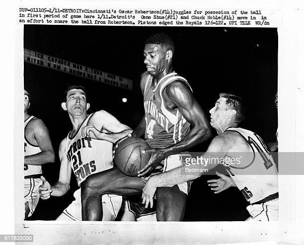 Cincinnati's Oscar Robertson juggles for possession of the ball in the first period of the game here 1/11 Detroit's Gene Shue and Chuck Noble move in...
