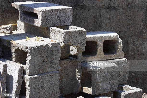 Cinderblocks piled one upon another on a forgotten construction site